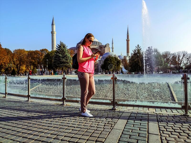 Adult young woman looks at the phone screen on the background of Hagia Sophia in Istanbul. Pretty tourist in Sultanahmet Square on. A sunny autumn day, concept stock image