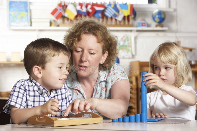 Adulte aidant deux enfants en bas âge à Montessori/Pr images stock