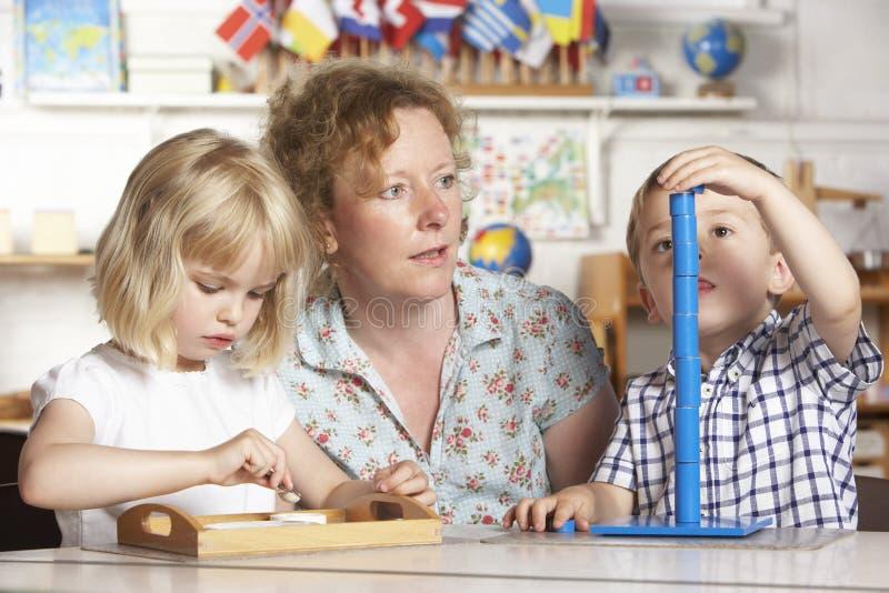 Adulte aidant deux enfants en bas âge chez Montessori/pré images libres de droits