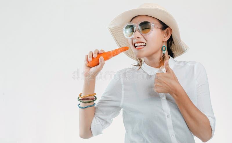 Adulte asiatique utilisant un chapeau du soleil et mangeant des carottes sur le fond blanc photographie stock libre de droits