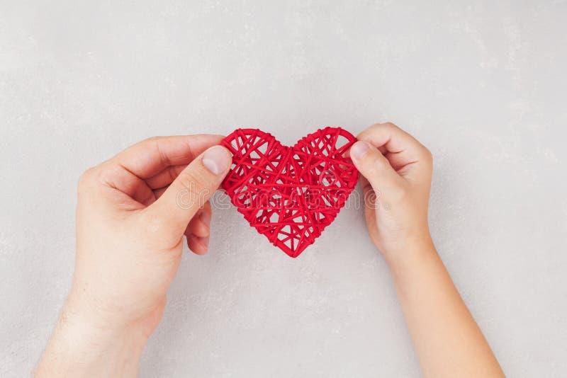 Adulte et enfant tenant le coeur rouge dans des mains d'en haut Liens de parenté, soins de santé, concept pédiatrique de cardiolo photos libres de droits