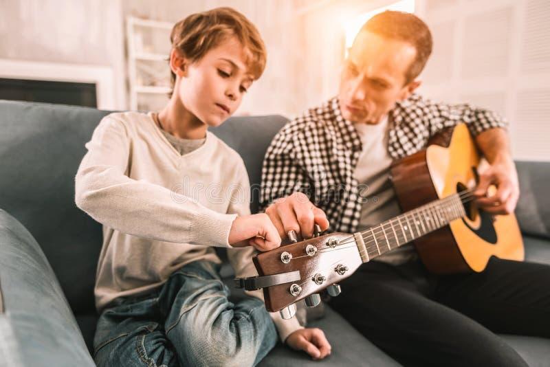 Adulte imaginatif enseignant à son enfant curieux les complexités de la guitare photos libres de droits