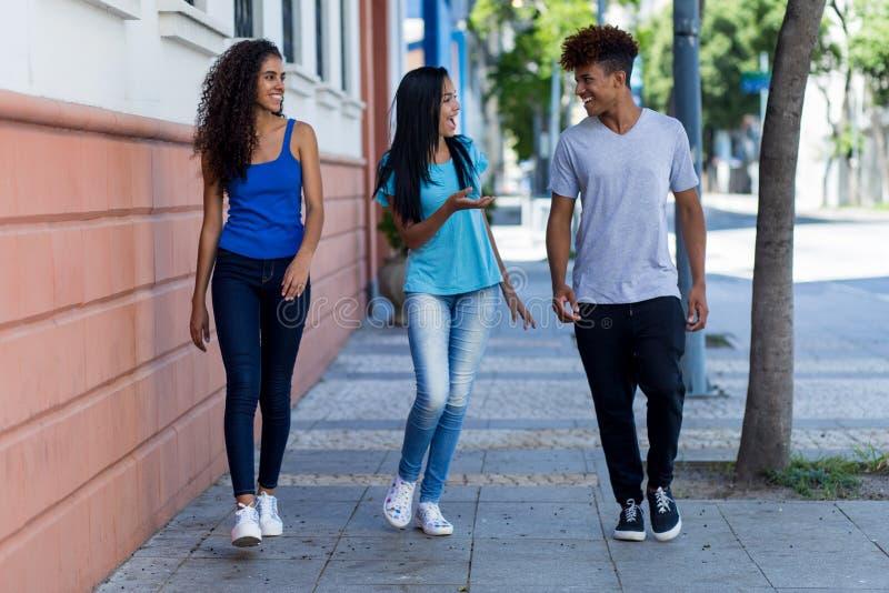 Adulti e dei pantaloni a vita bassa ispanici afroamericani e latini di conversazione giovani in città fotografie stock
