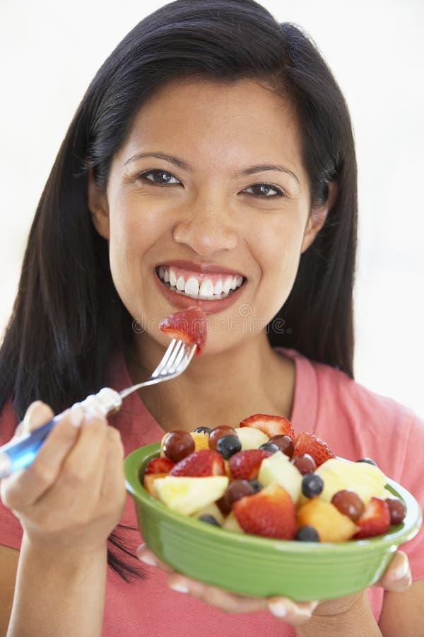 adulto che mangia la metà di donna dell'insalata della frutta fresca fotografia stock libera da diritti