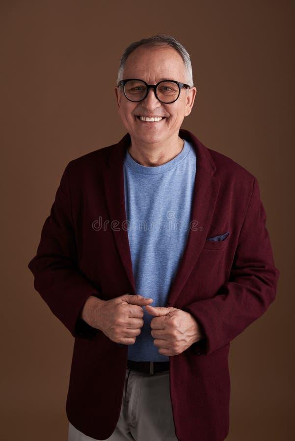 Adulto hermoso que sonríe y que presenta en la chaqueta marrón foto de archivo libre de regalías