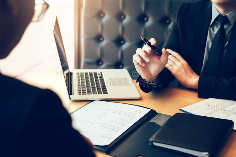 Adulto joven asiático que se sienta en el escritorio a través del encargado que es entrevista de trabajo entrevistada con en siti foto de archivo libre de regalías