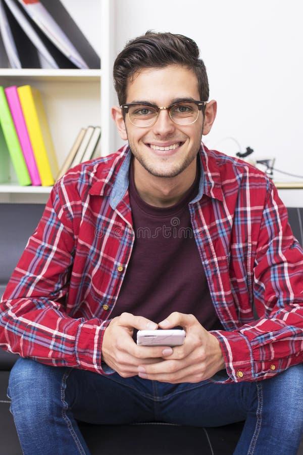 Adulto joven con el teléfono móvil fotografía de archivo libre de regalías