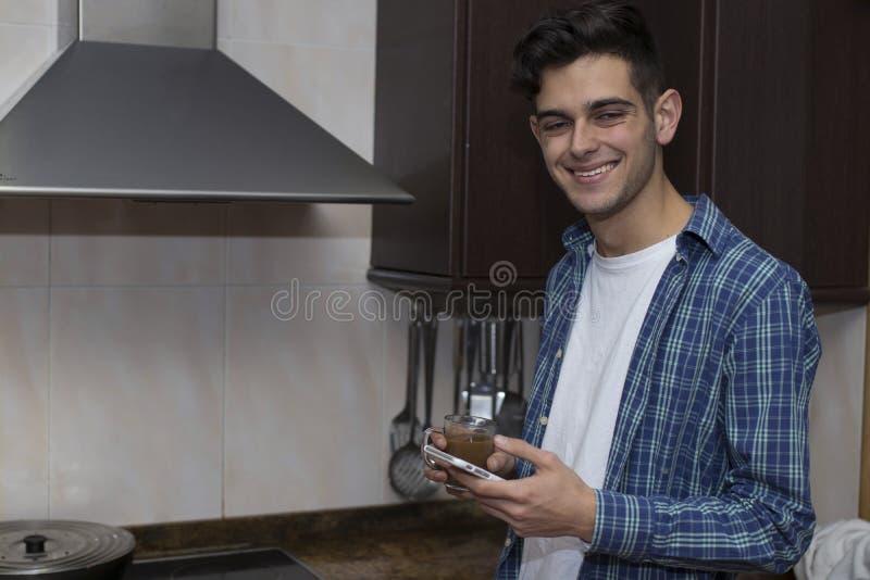 Adulto joven con el teléfono móvil en cocina imagen de archivo libre de regalías
