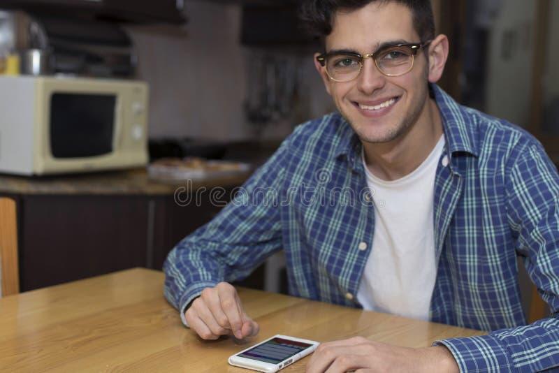 Adulto joven con el teléfono móvil en cocina imágenes de archivo libres de regalías