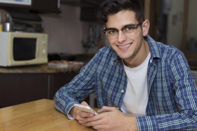 Adulto joven con el teléfono móvil en cocina fotografía de archivo libre de regalías