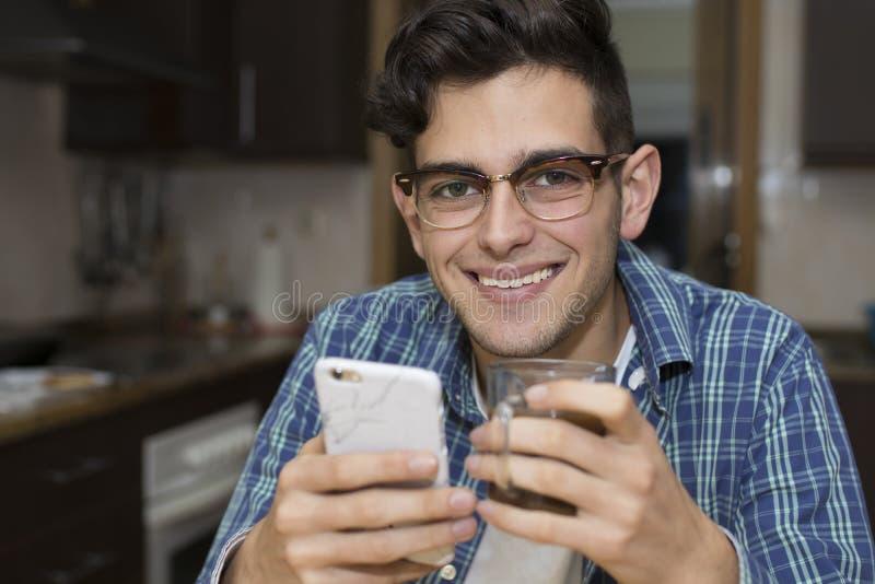 Adulto joven con el teléfono móvil en cocina foto de archivo