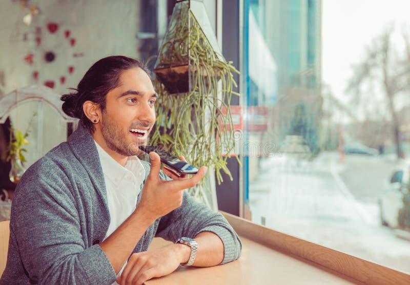 Adulto joven latinoamericano que usa el reconocimiento vocal en el teléfono foto de archivo