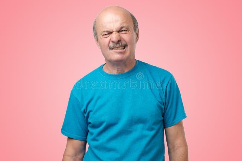 Adulto maduro no t-shirt azul que tem uma dúvida com aversão na posição da cara no fundo cor-de-rosa foto de stock royalty free