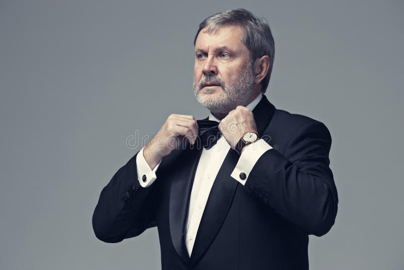 Adulto maschio invecchiato mezzo che indossa un vestito isolato su gray immagini stock libere da diritti