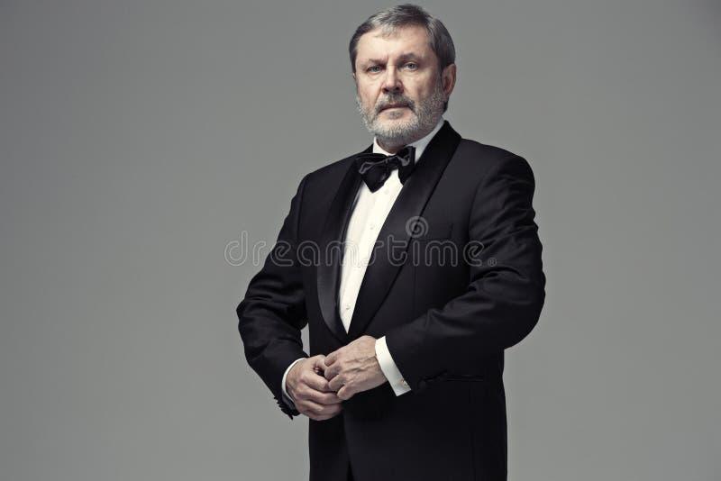 Adulto maschio invecchiato mezzo che indossa un vestito isolato su gray fotografie stock