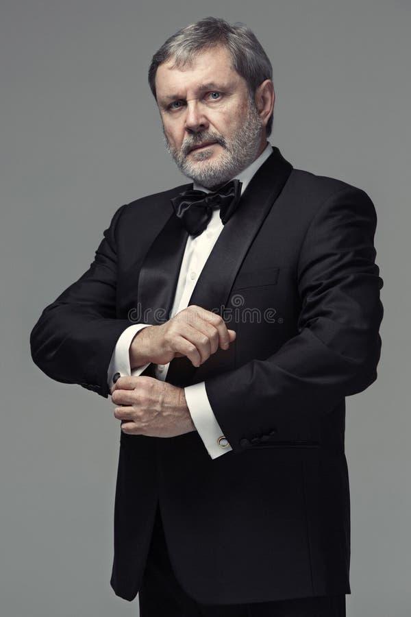Adulto maschio invecchiato mezzo che indossa un vestito isolato su gray fotografia stock libera da diritti