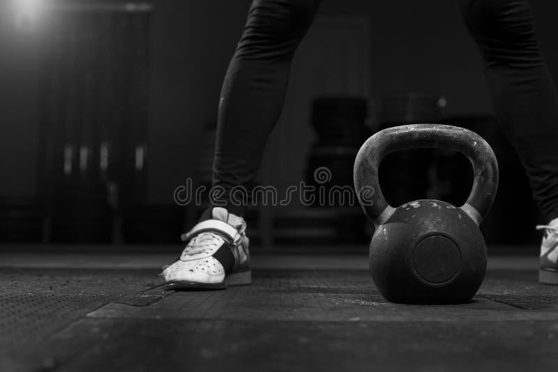 Adulto masculino muscular que ejercita con la campana de la caldera imagen de archivo