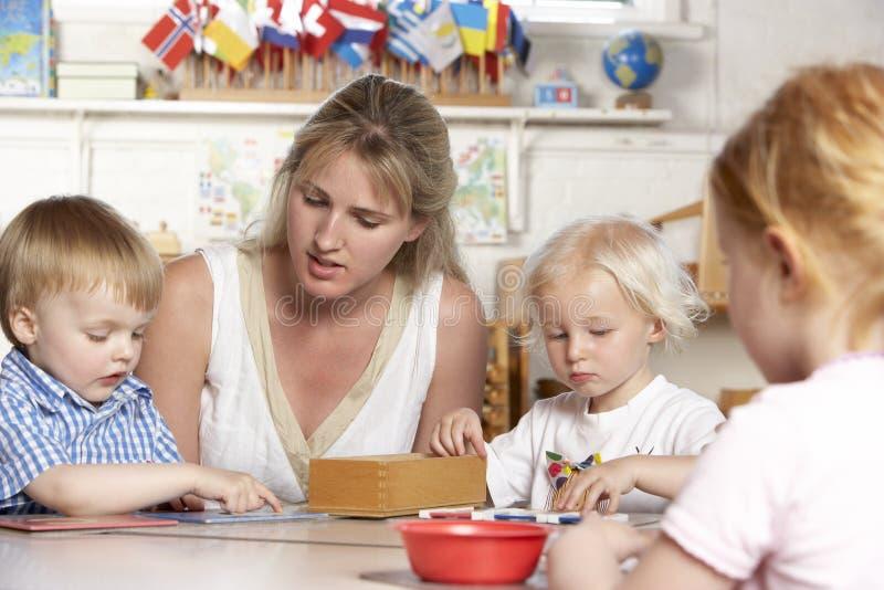 Adulto que ayuda a niños jovenes en Montessori/Pre-Sch foto de archivo libre de regalías