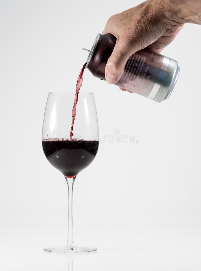 Adulto senior che versa un vetro di vino rosso da una latta di alluminio fotografie stock