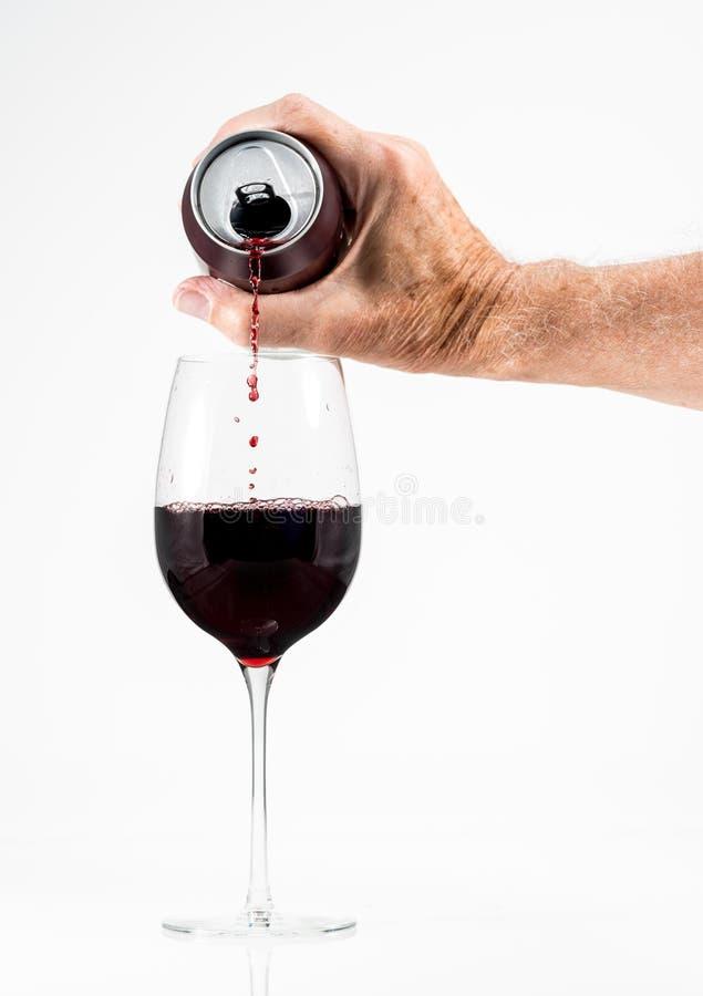 Adulto senior che versa un vetro di vino rosso da una latta di alluminio immagine stock libera da diritti