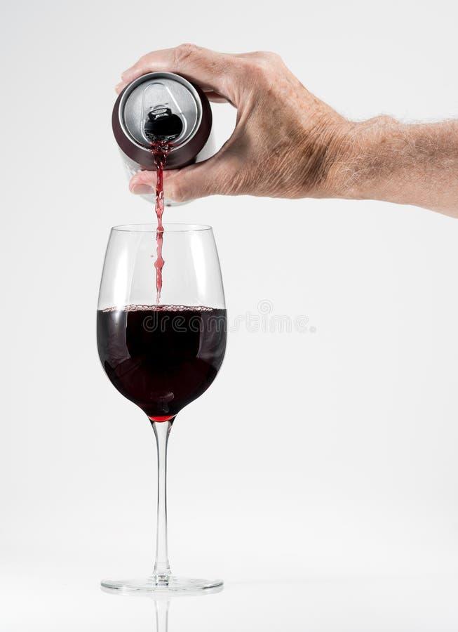 Adulto senior che versa un vetro di vino rosso da una latta di alluminio fotografie stock libere da diritti