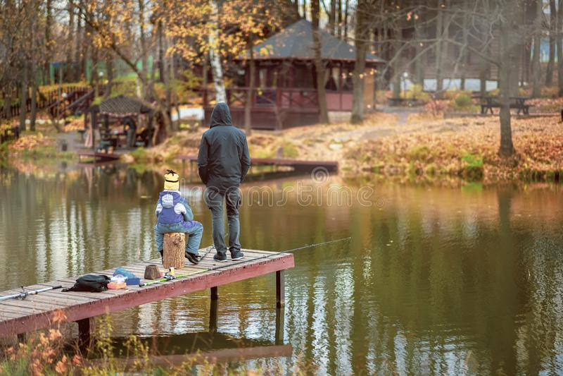 Adulto y niño en un embarcadero de madera, pescando el puente Parque del oto?o Hojas caidas, día soleado, fondo natural foto de archivo
