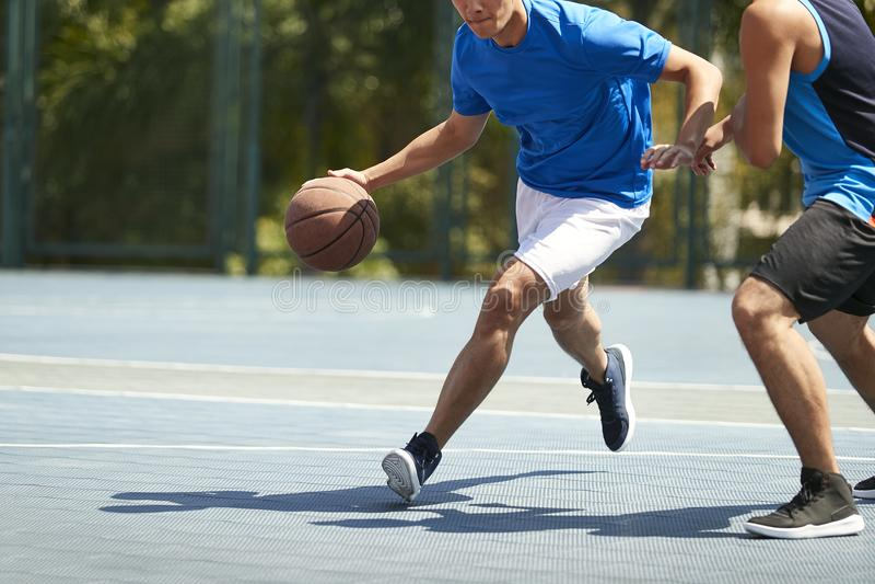 Adultos asiáticos novos que jogam o basquetebol fotos de stock