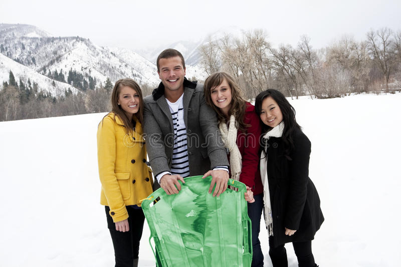 Adultos jovenes en la nieve del invierno sledding imagenes de archivo