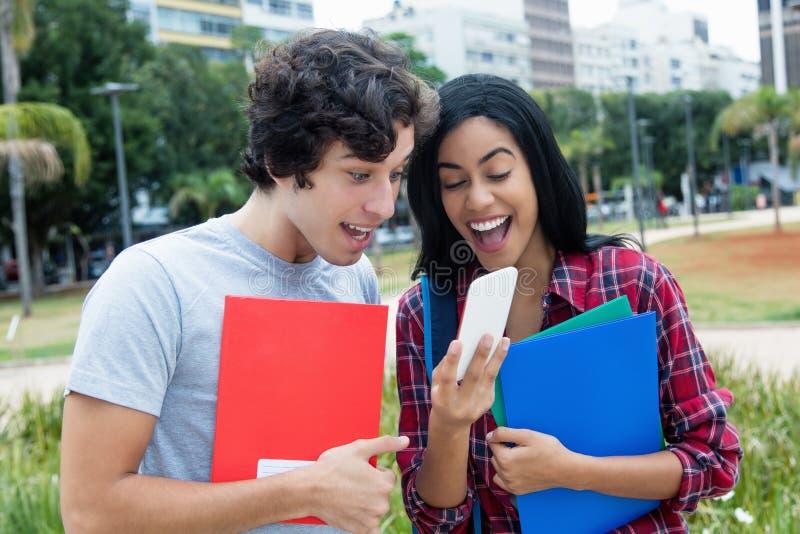 Adultos jovenes felices que reciben buenas noticias en el teléfono foto de archivo