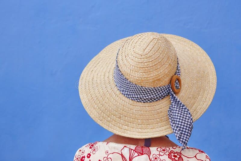 Adultos jovenes Mujer con el sombrero y el fondo azul Relajación fotografía de archivo libre de regalías