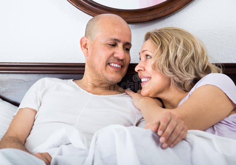Adultos maduros que encontram-se na cama da família fotos de stock