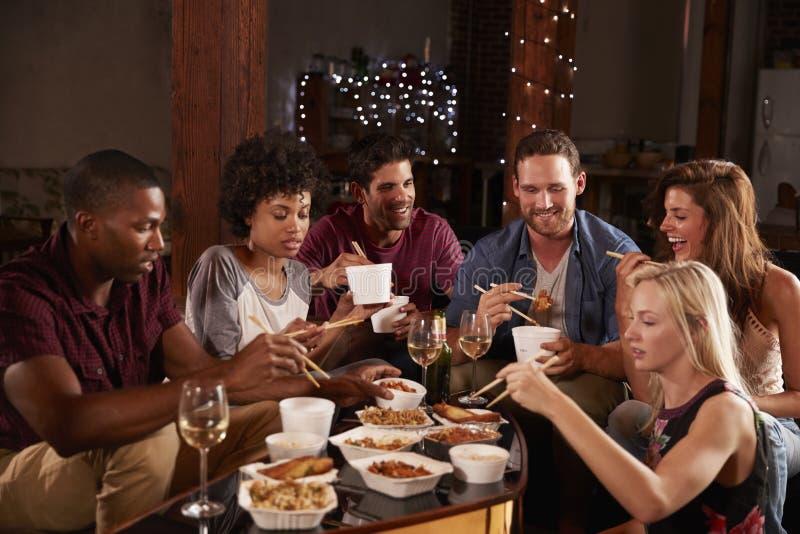Adultos novos que comem afastado chinês em um partido em casa imagens de stock