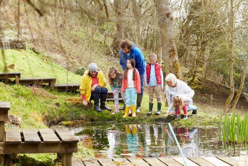 Adultos y niños que exploran la charca en el centro de la actividad fotografía de archivo