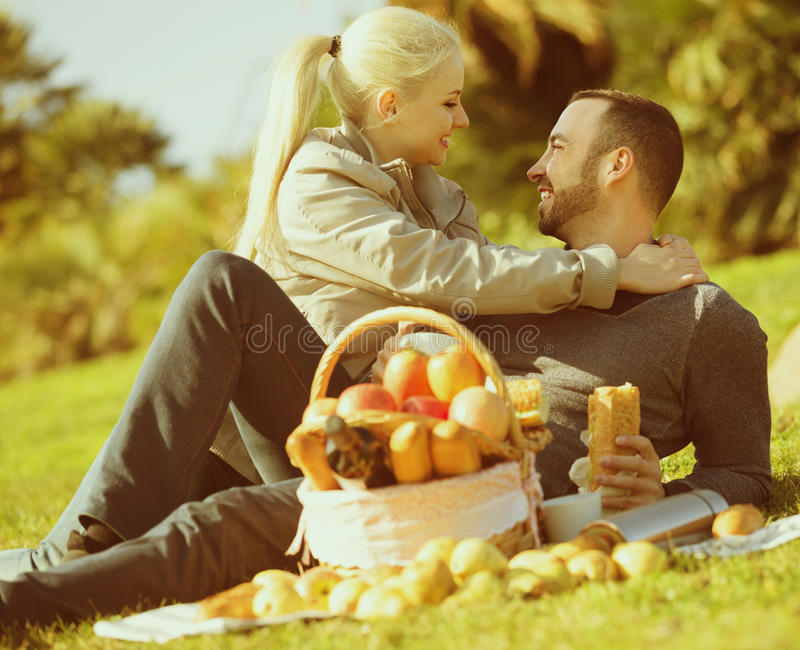 Adults with apples in nature. Portrait of young adults with apples and sandwitches in nature together stock photography