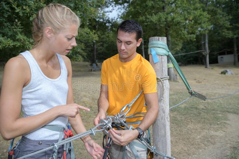 Adults attaching safety clips to zip wire. Adult royalty free stock photography
