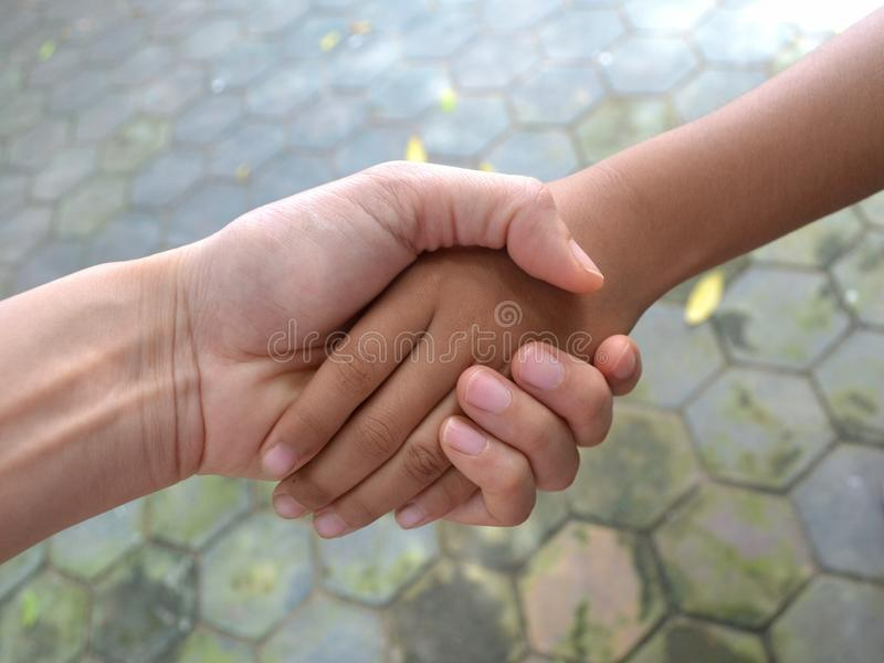 Adults Shake Hands With Children. Adults and children hold hands. Adults shake hands with children stock photos