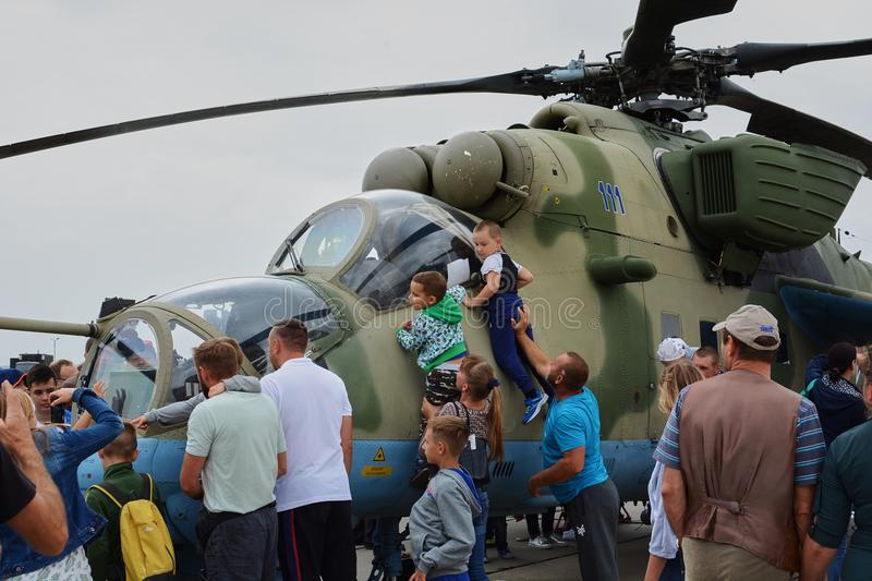Adults and children watch mi-24 helicopter stock image