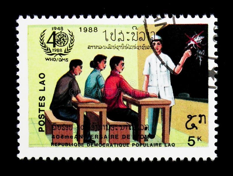 Adults in hygiene class, 40th anniversary of W.H.O. serie, circa. MOSCOW, RUSSIA - NOVEMBER 25, 2017: A stamp printed in Lao People's Democratic Republic shows royalty free stock image