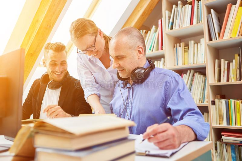 Adults learn together for further education. In the library royalty free stock images