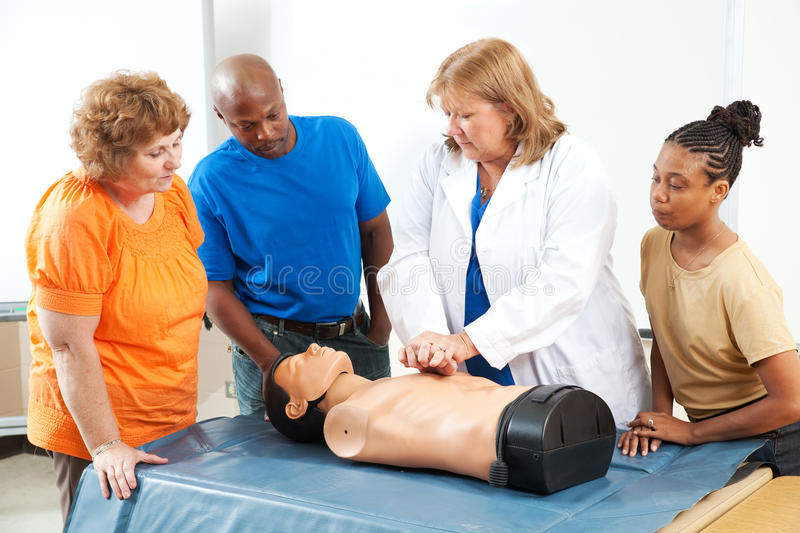 Adults Learning First Aid CPR. Adult education students learning CPR and first aid from a doctor or nurse royalty free stock photos
