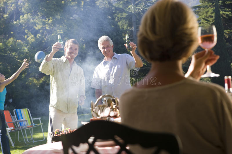 Adults raising wine glasses in toast at family barbecue in garden, girl (11-13) playing with ball in background (tilt) stock images
