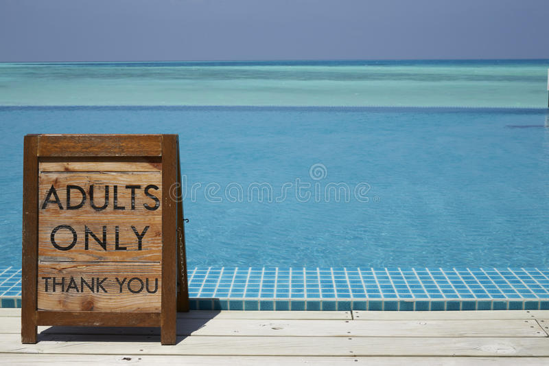Adults only sign by an infinity pool with ocean beyond stock images