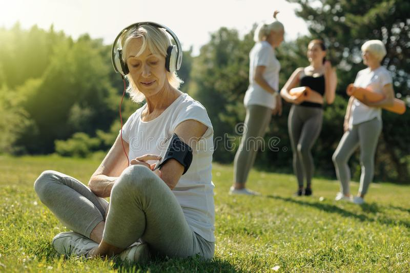 Advanced retired lady turning music before training session royalty free stock image