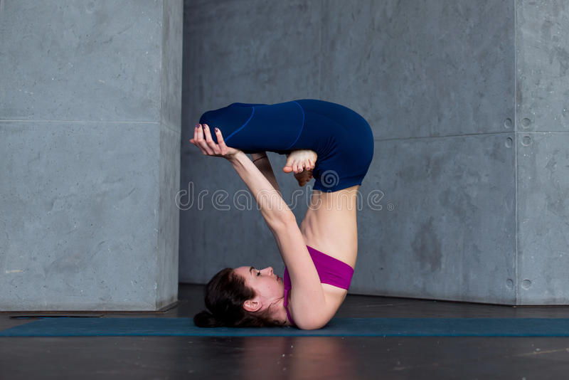 Download Advanced Young Yogini Practicing Hatha Yoga Standing In Inverted Lotus Pose Padmasana On