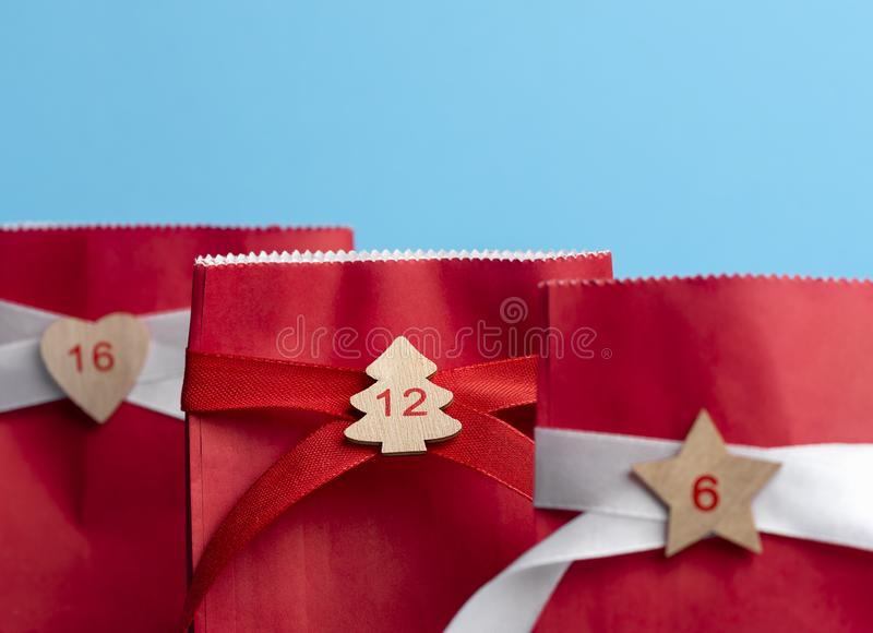 Advent calendar gift bags. Red paper bags with numbers. Gifting royalty free stock photo
