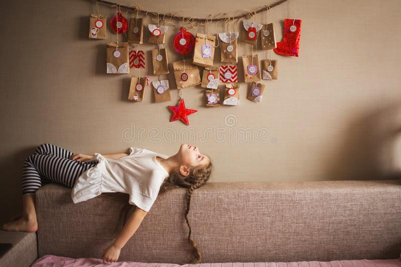 The advent calendar hanging on the wall. small gifts surprises for children. girl lies and looks at the calendar stock photography