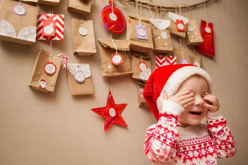 Advent calendar for kids. child in a Christmas cap and pajamas happy and playing peek a Boo.  royalty free stock photo