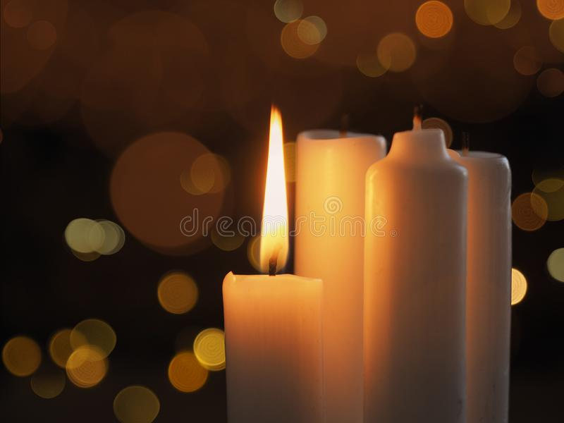 First Advent candle. Advent candle on a blurred bokeh background, one candle is burning, Christmas time background stock image