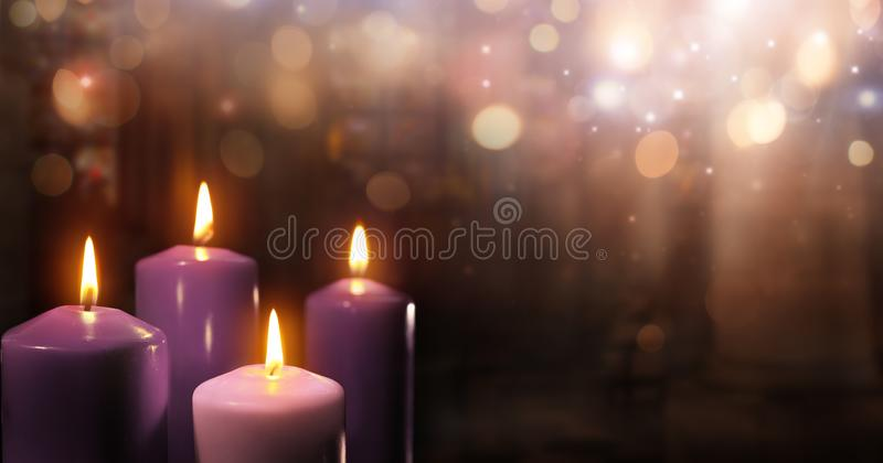 Advent Candles In Church - Three Purple And One Pink. As A Catholic Symbol And Bokeh Lights royalty free stock image