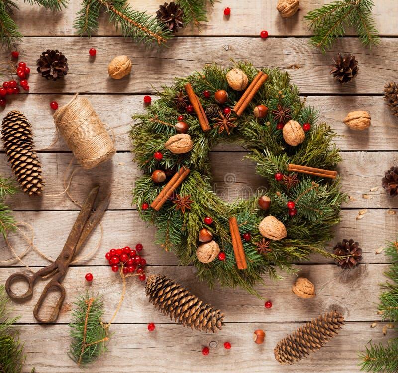 Advent Christmas kransgarnering med naturliga garneringar, sörjer kottegranen, muttrar, kanderad frukt på träbakgrund arkivbilder